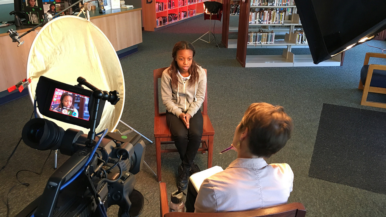 Student being interviewed by WFSU staff in a school library.