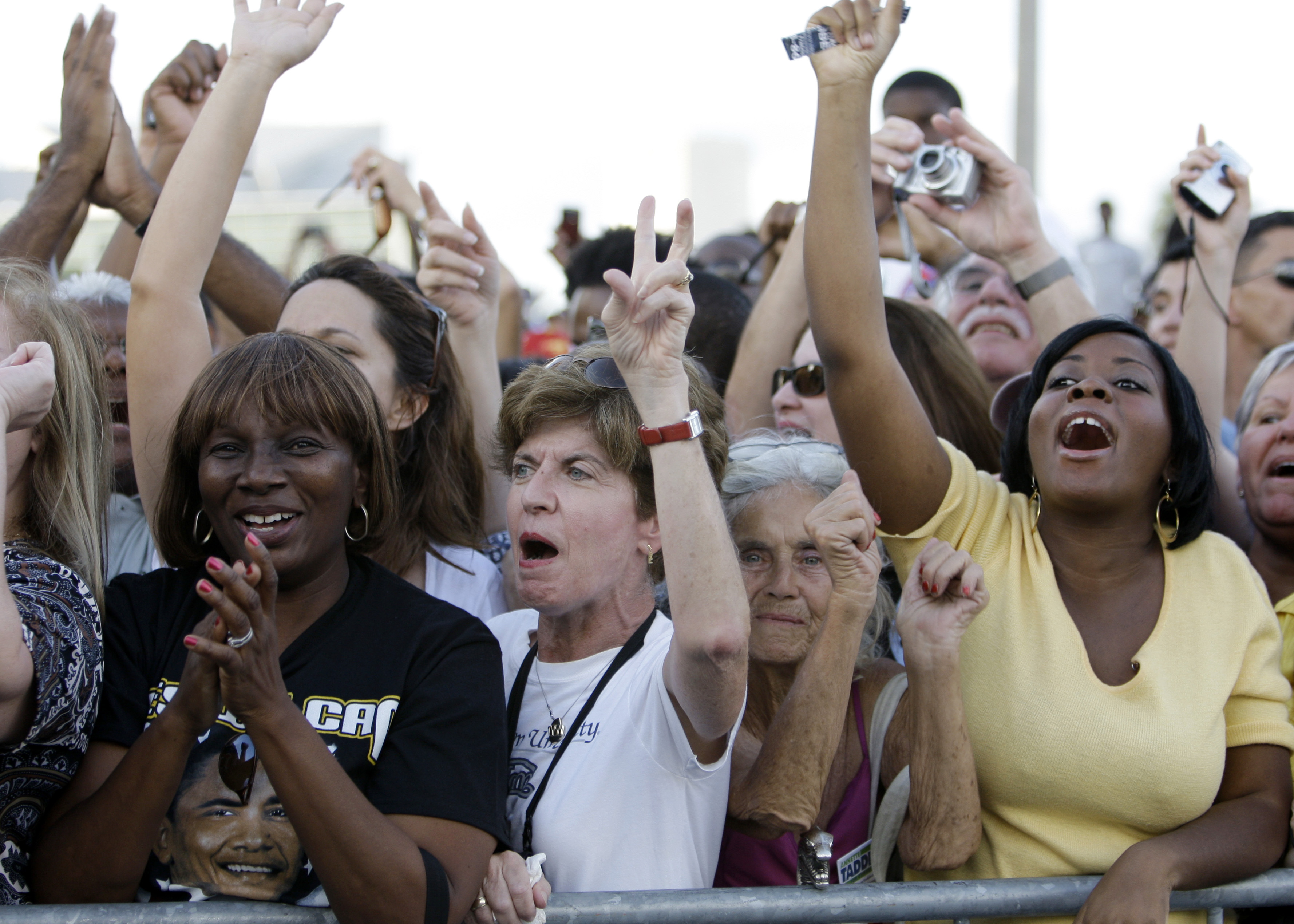 mostly women in a crowd cheering, waving, and screaming at a rally for the 2008 democratic candidate barack obama