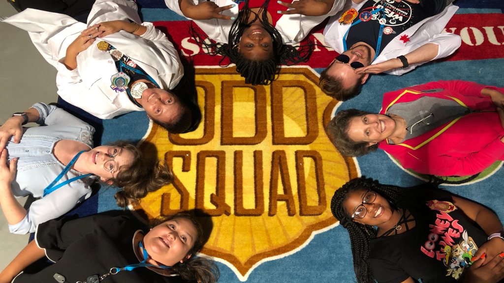 A group of people laying down in a circle around a carpet that says