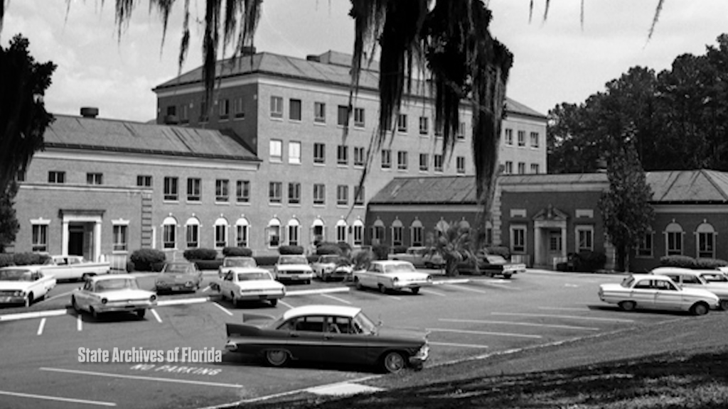 black and white photo of large brick building with cars from the 1950's parked in front.