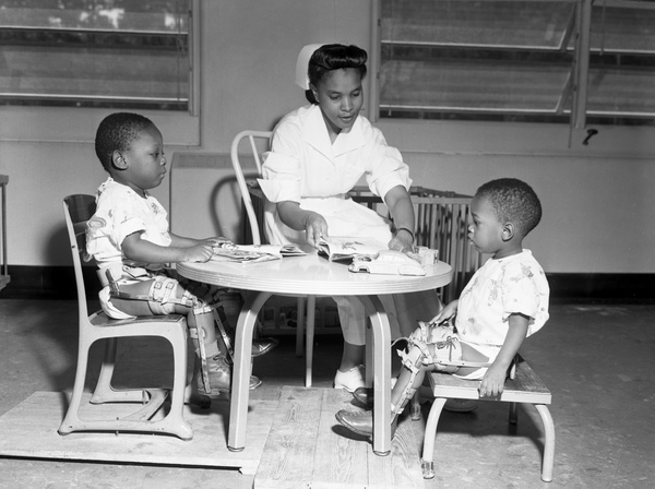 A nursing sitting at  little table with two children with braces on their legs.