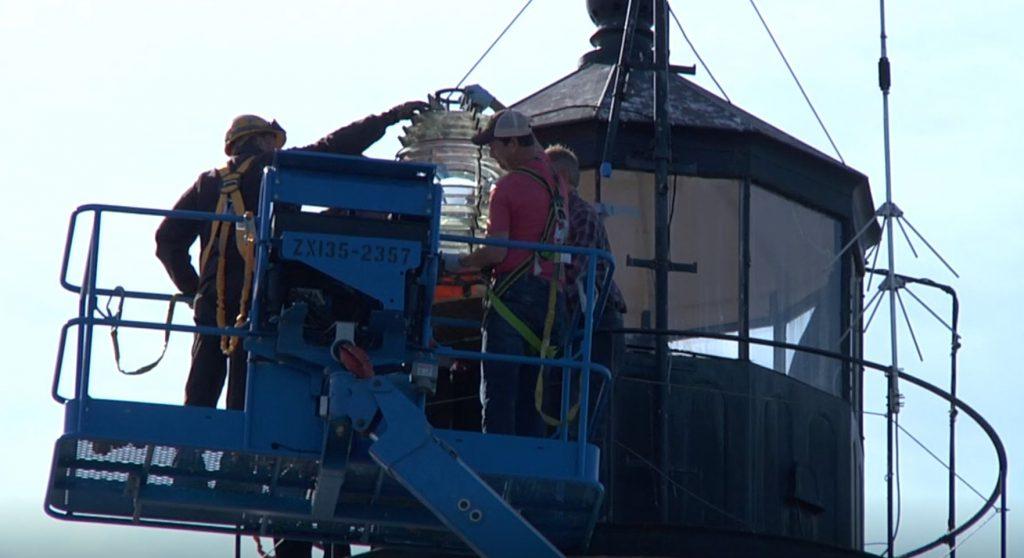 three men remove Fresnel Lens from lighthouse light room using lift.