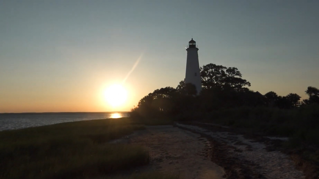 A sunset over a the Apalachee  Bay with the white tower of a lighthouse in the foreground.