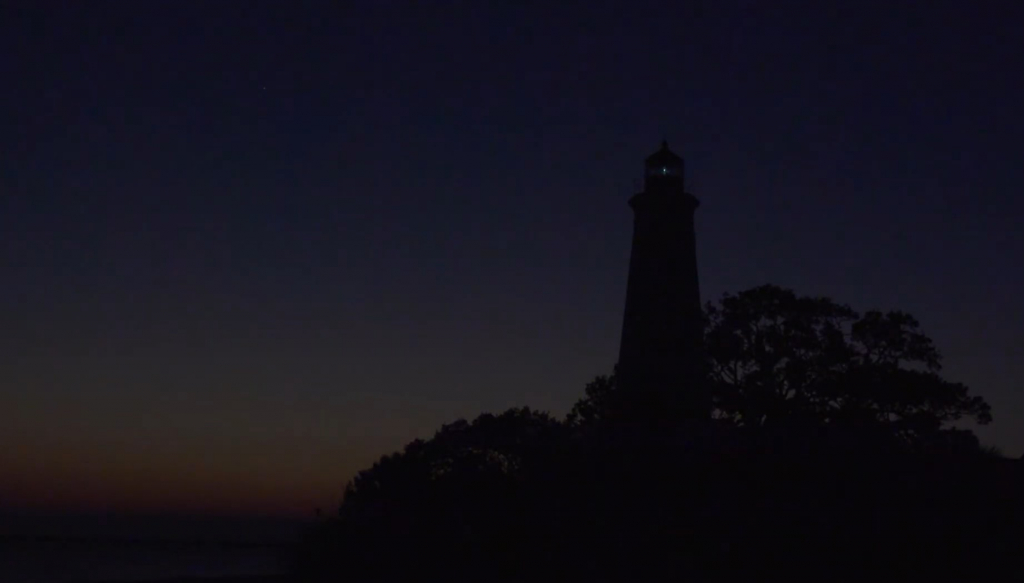 Silhouette of a lighthouse against the darkened sky moments after the sun dips behind the horizon.  There is a pinprick of light coming from the lamp room of the lighthouse
