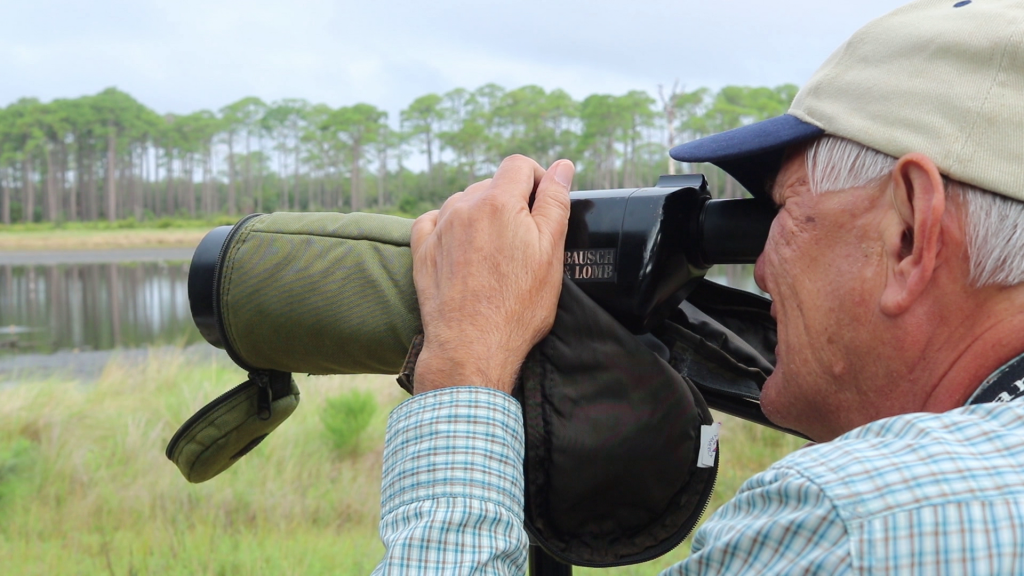 A man looking through a large viewfinder at trees. He is wearing a tan baseball cap and a plaid shirt.