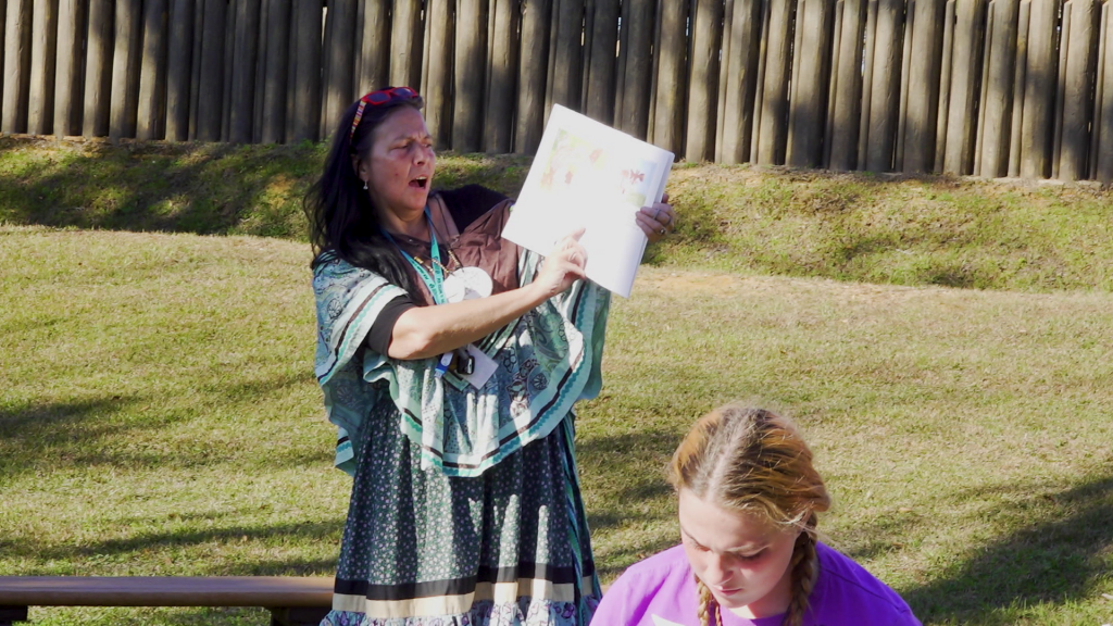 A woman showing the page of a book and young woman in front of her.
