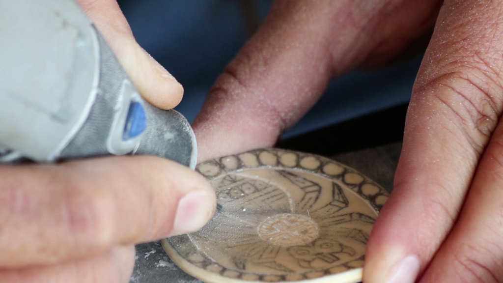 A close up of a hand carving a shell