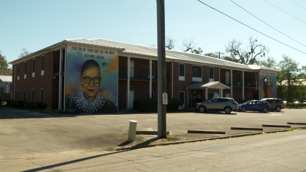 A building that has two giant murals  on the walls and three cars in the front.