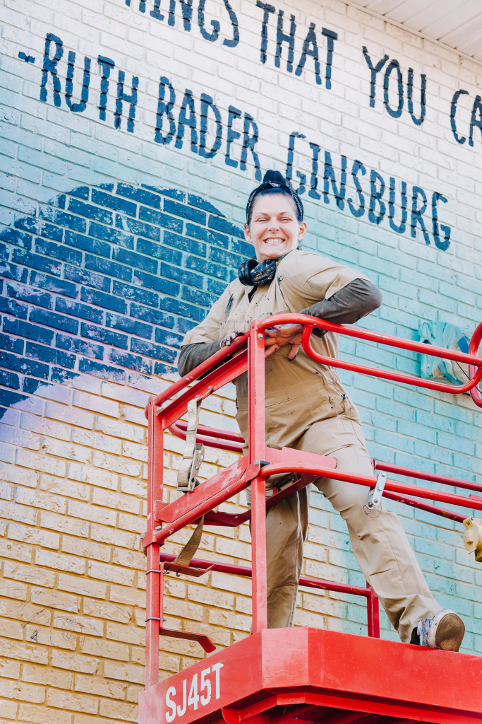 Woman smiling  on scafolding in front of  a mural.