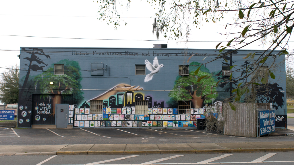 A building with a mural of a hand and a dove. and trees.