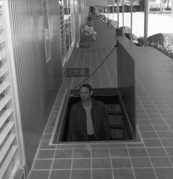 A man emerging from underground staircase at a motel.