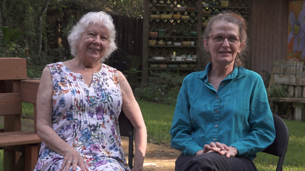 Two older women sitting on outdoors.