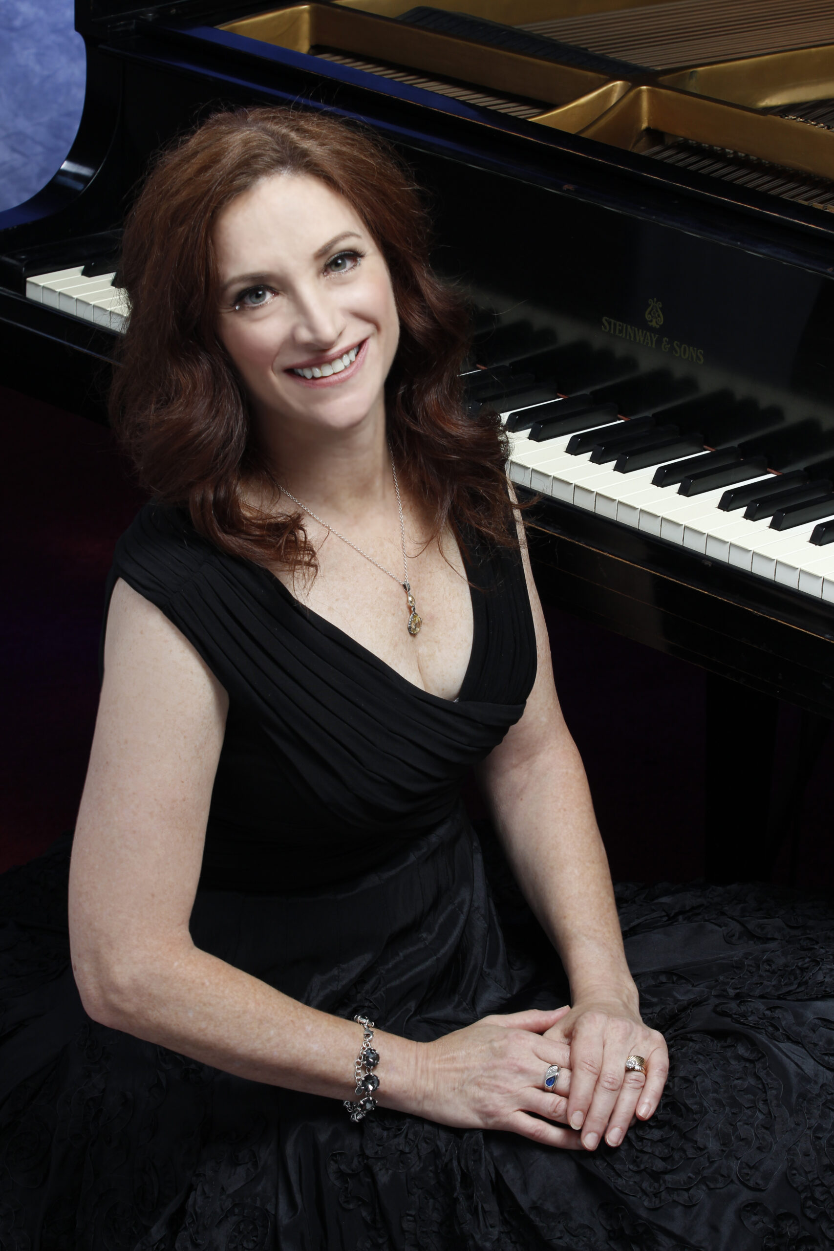 Robin Spielberg standing in front of a piano