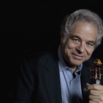 Itzhak Perlman wearing a suit and tie holding a cell phone