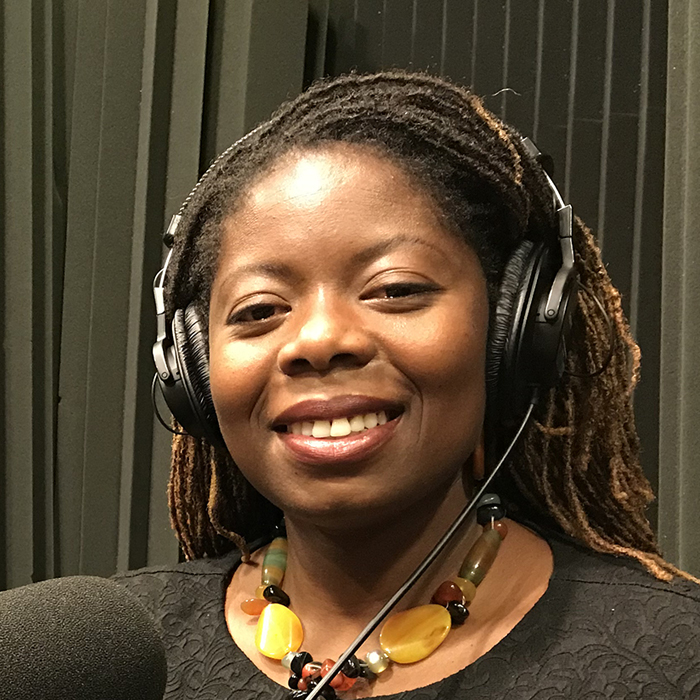 Abena sitting in the studio by the microphone with headphones on