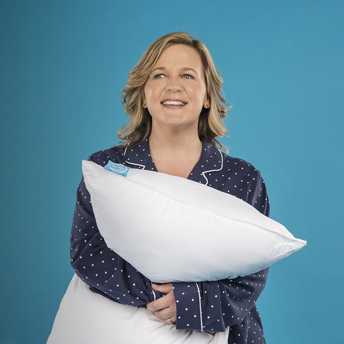 woman smiling and holding a pillow
