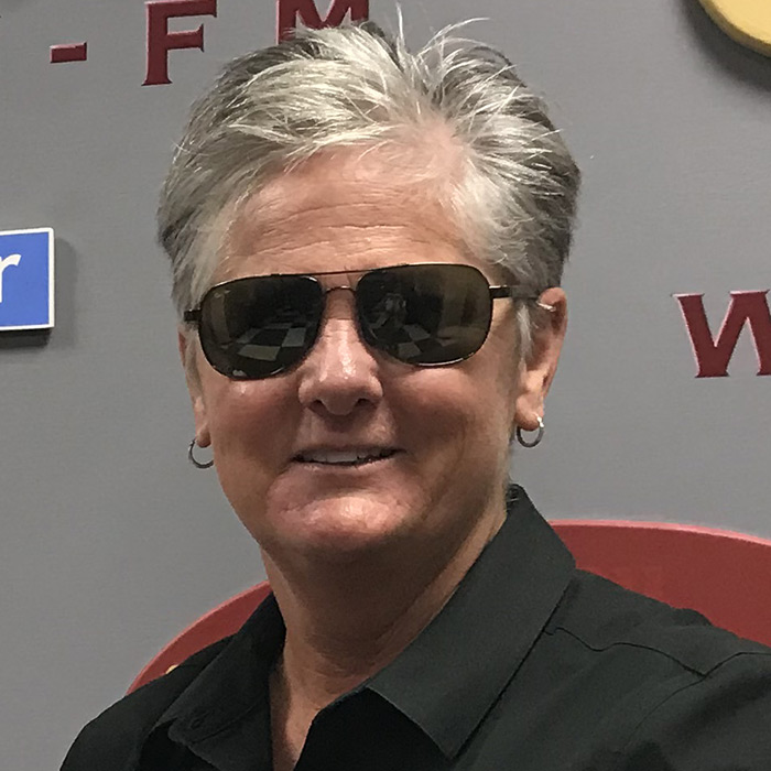 Chief Terri Brown wearing sunglasses in front of the WFSU logos, in the WFSU lobby.
