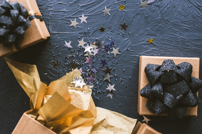 gifts on a black background with star confetti
