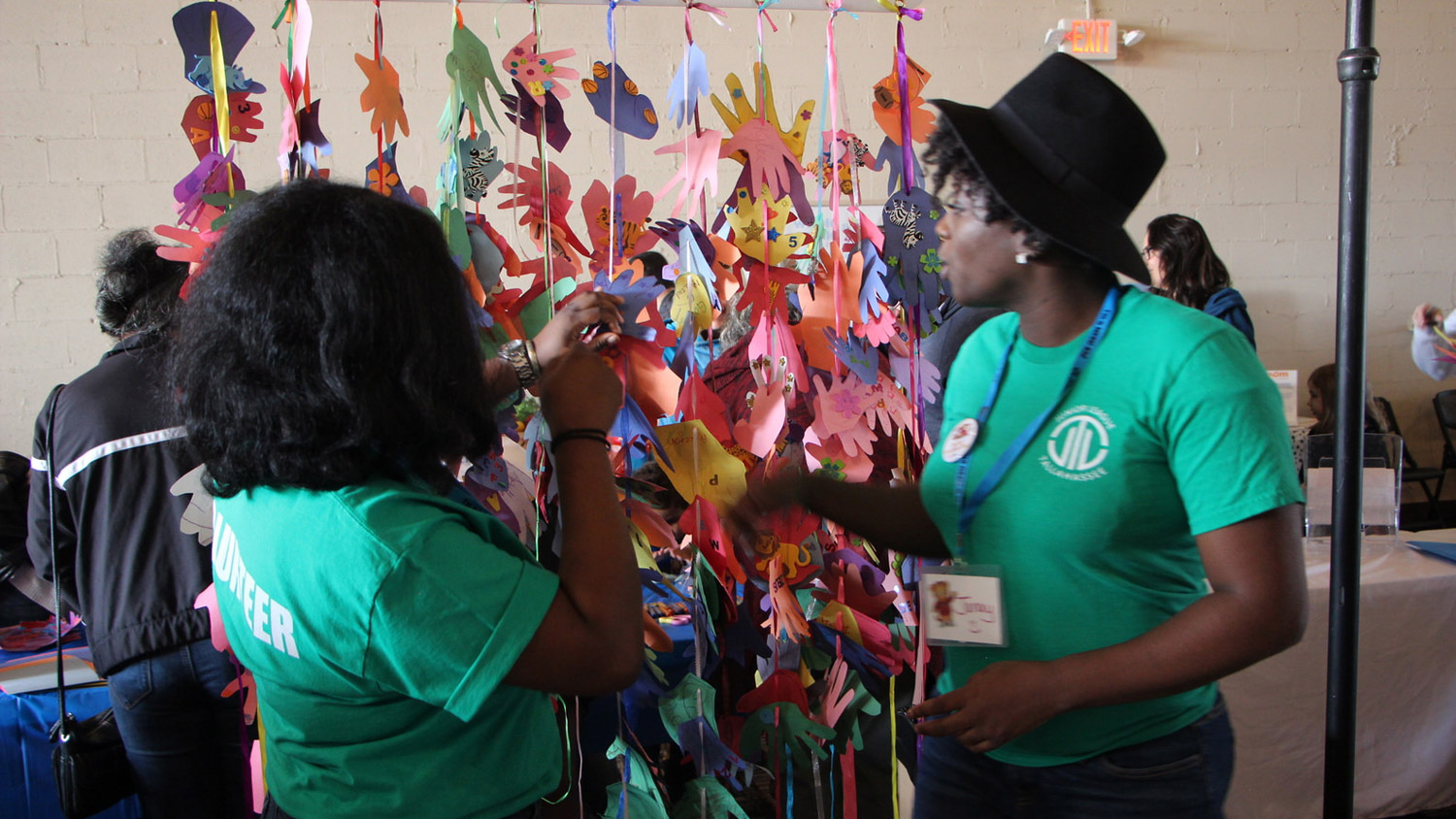 two women in green volunteer shirts next to strung up paper hands