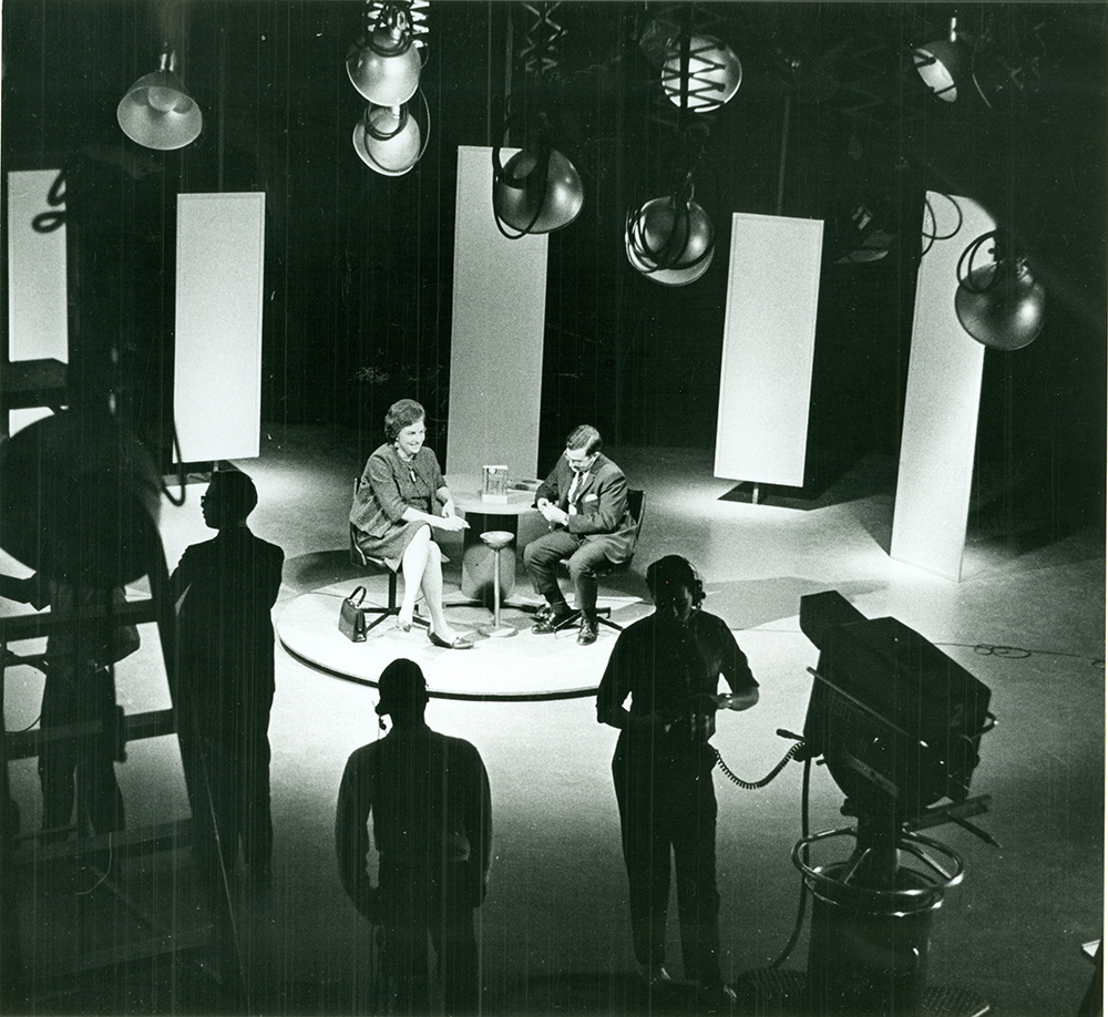 black and white photo of two people sitting at a table on a telelvisions set. others stand near tv cameras.