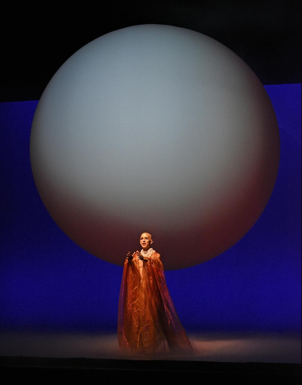 Person in red performing infront of a globular structure