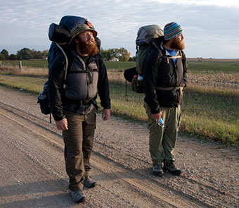 two bearded backpackers walking down a dirt road
