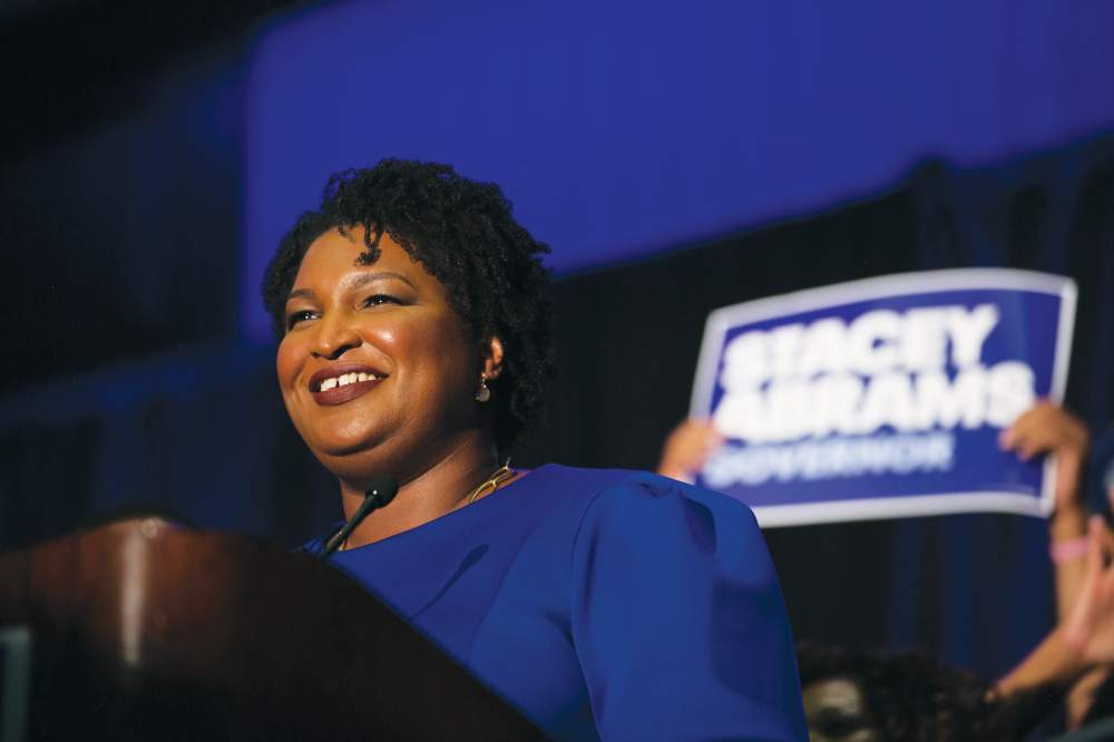 Woman standing in front of a sign that says Stacey Abrams