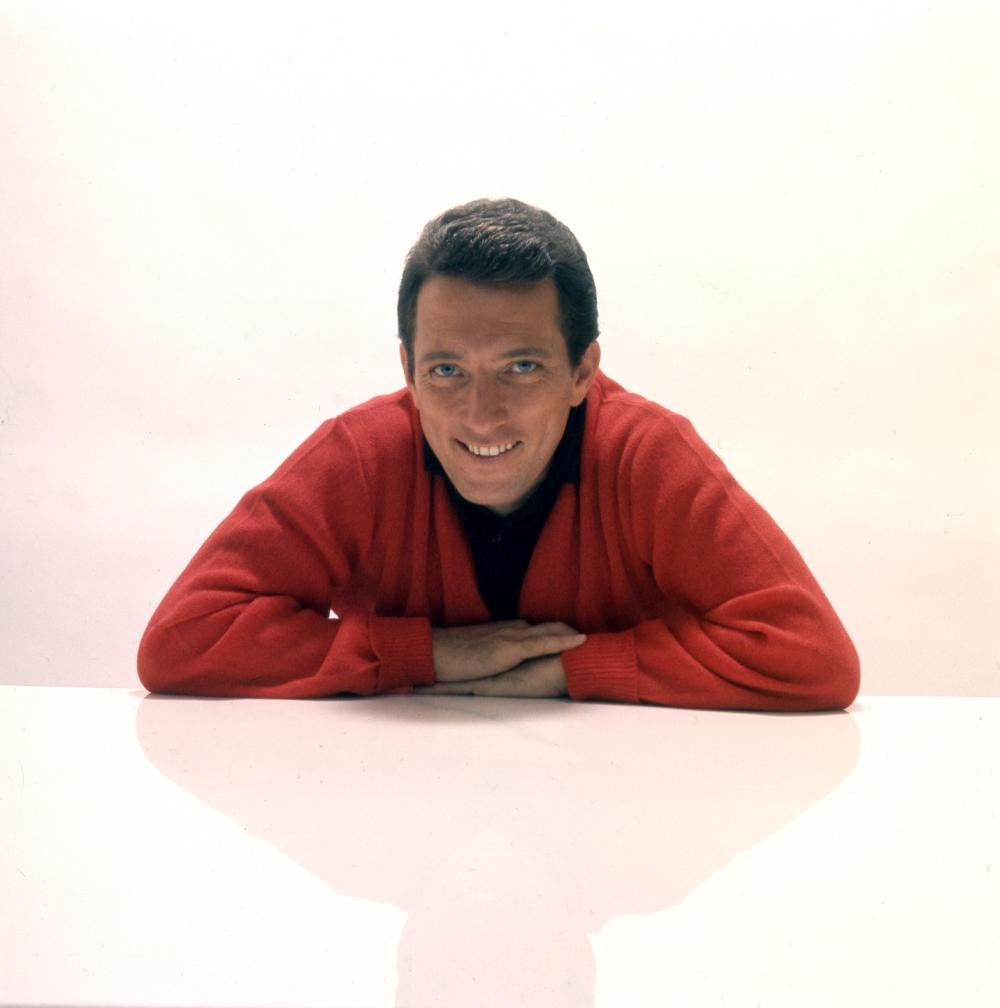 A man in red smiling at the camera