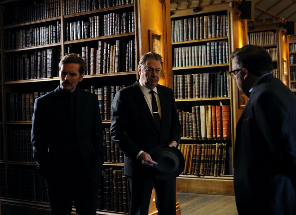 Three serious men in a library