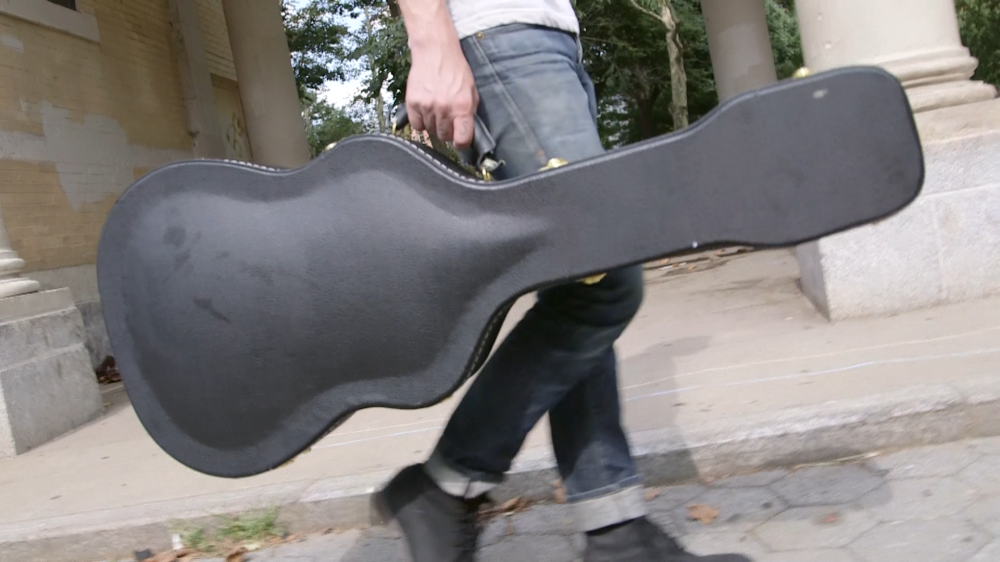 Picture of someone holding a guitar case, most likely with a guitar in it