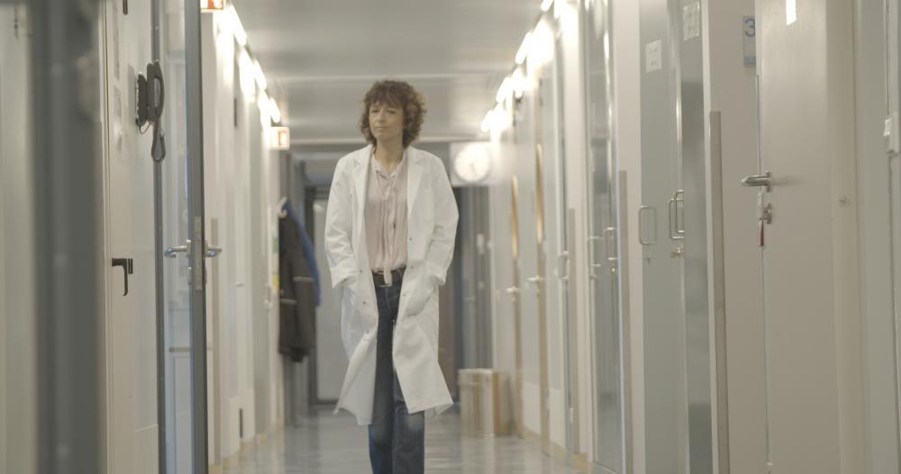 A woman walking down a brightly lit hallway