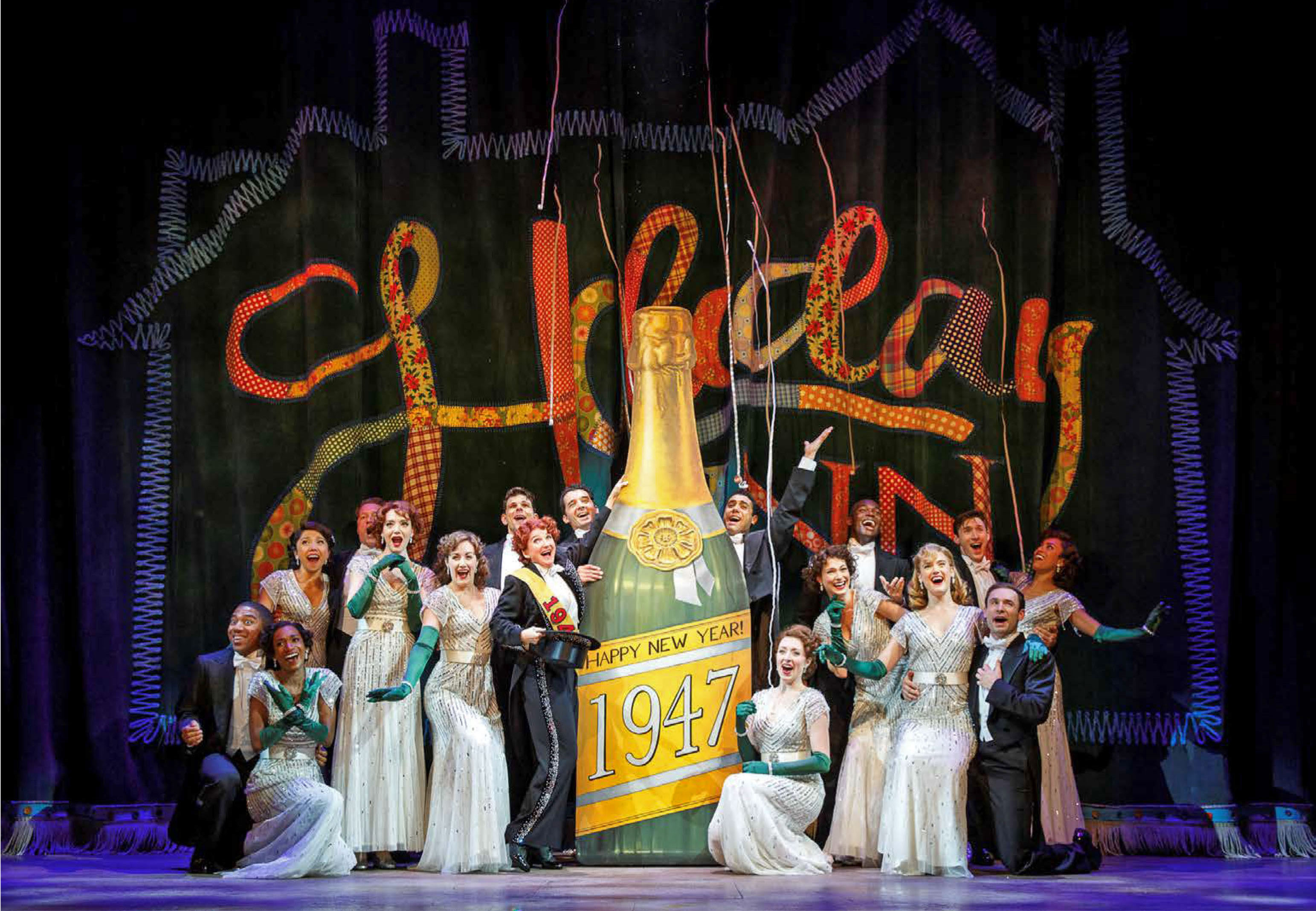 cast on stage with giant champagne bottle that reads 1947