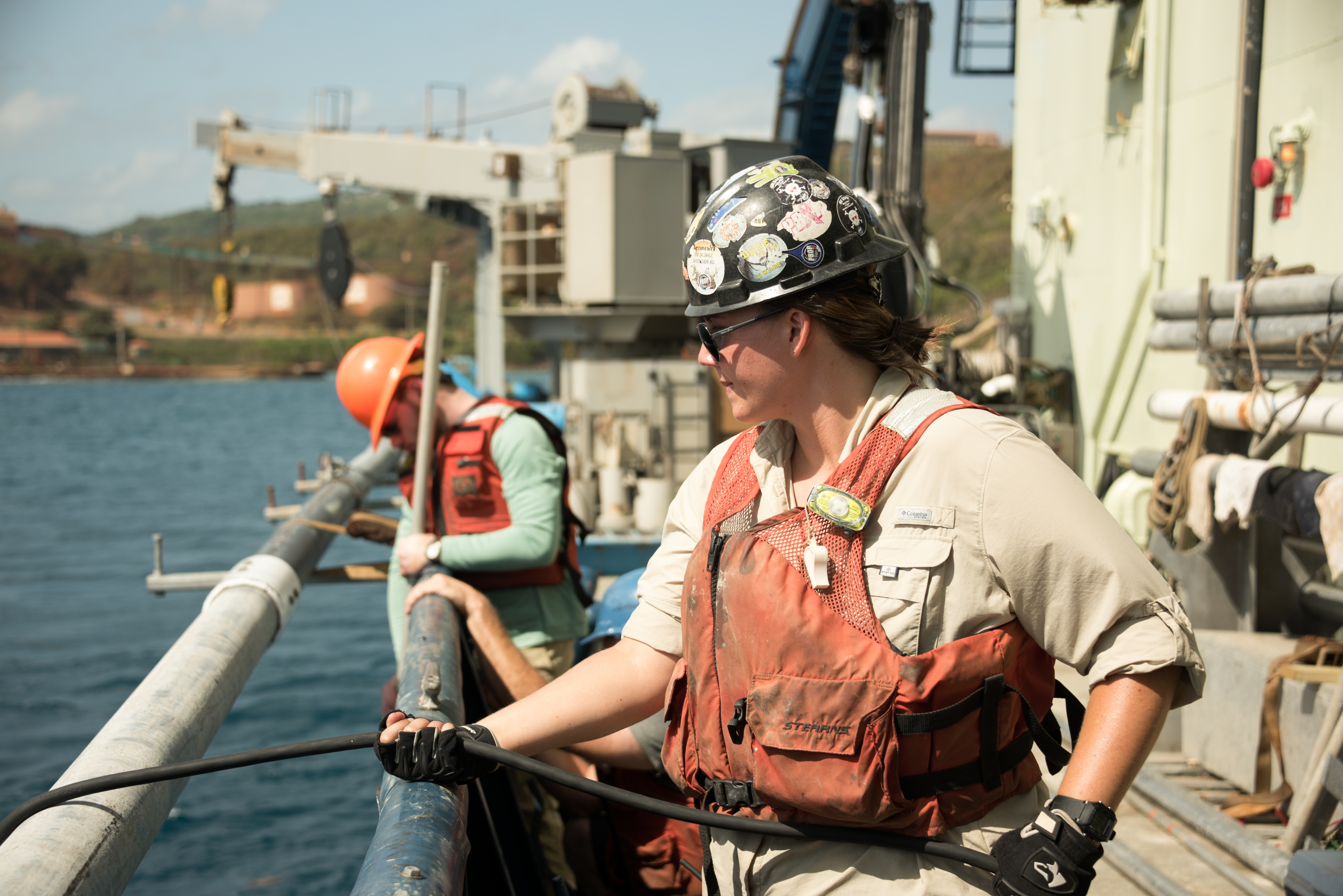 a woman in working gear pulling a line from a body of water
