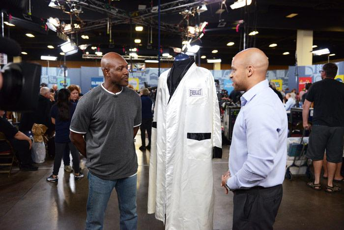 two men looking at a lab coat type smock on a mannequin