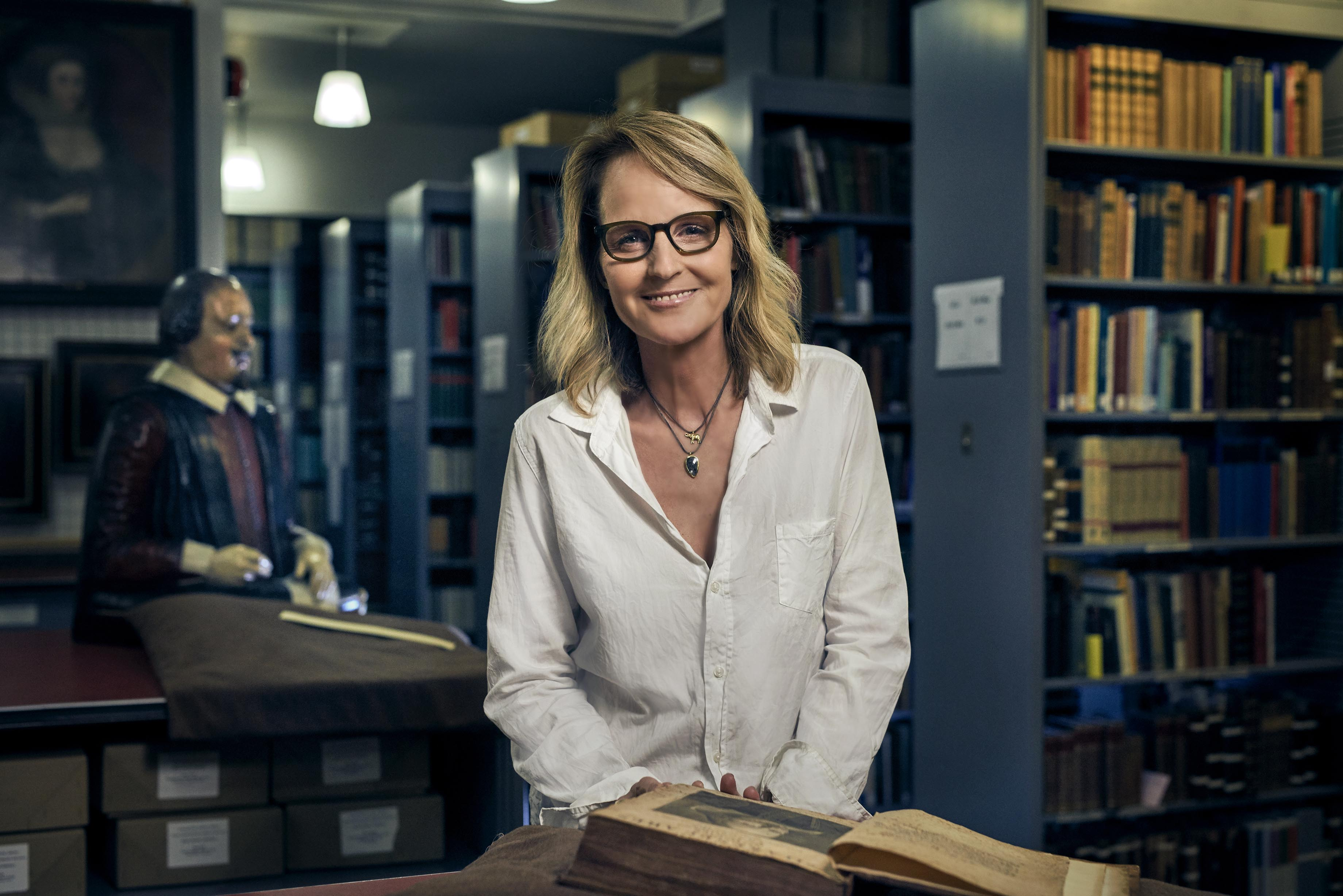 Helen Hunt sits at a table with bookshelves and a statue of Shakespeare behind her