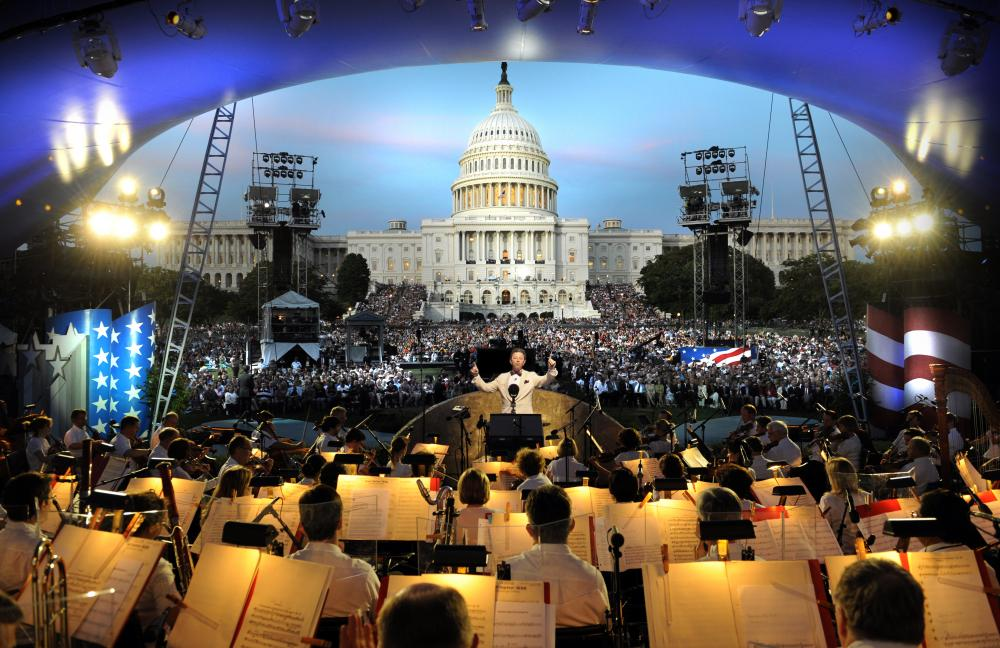 Conductor conducting an orchestra in front of the U.S capitol