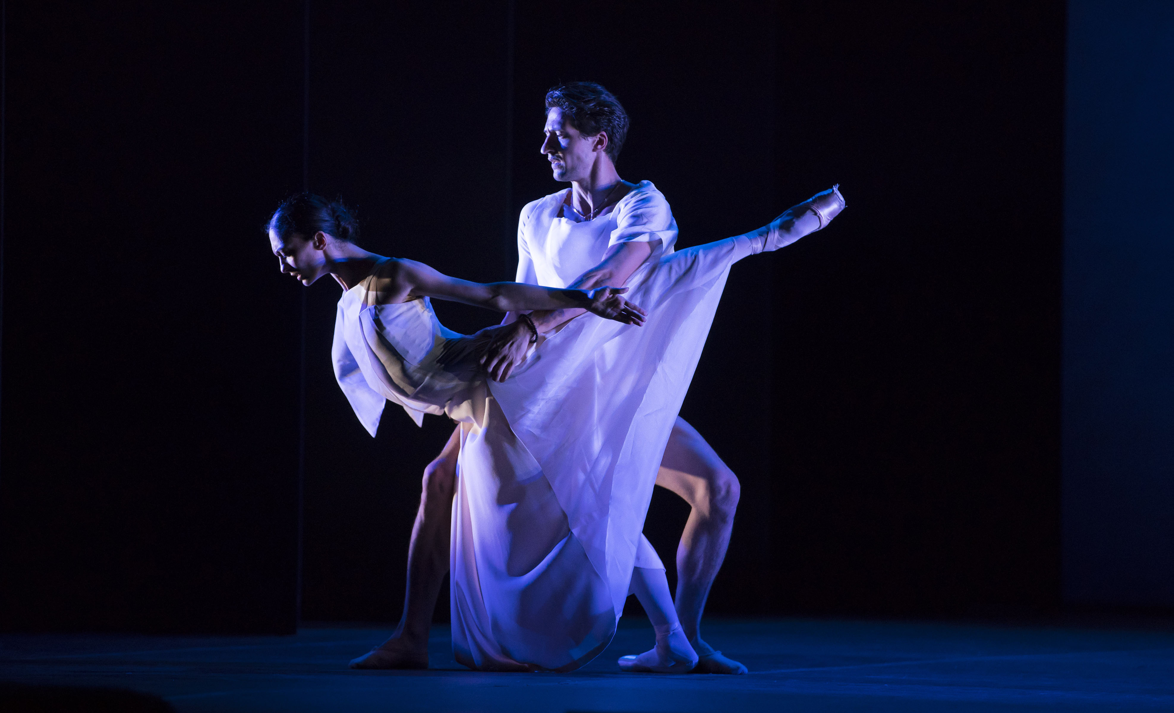 two dancers in white on a dark stage