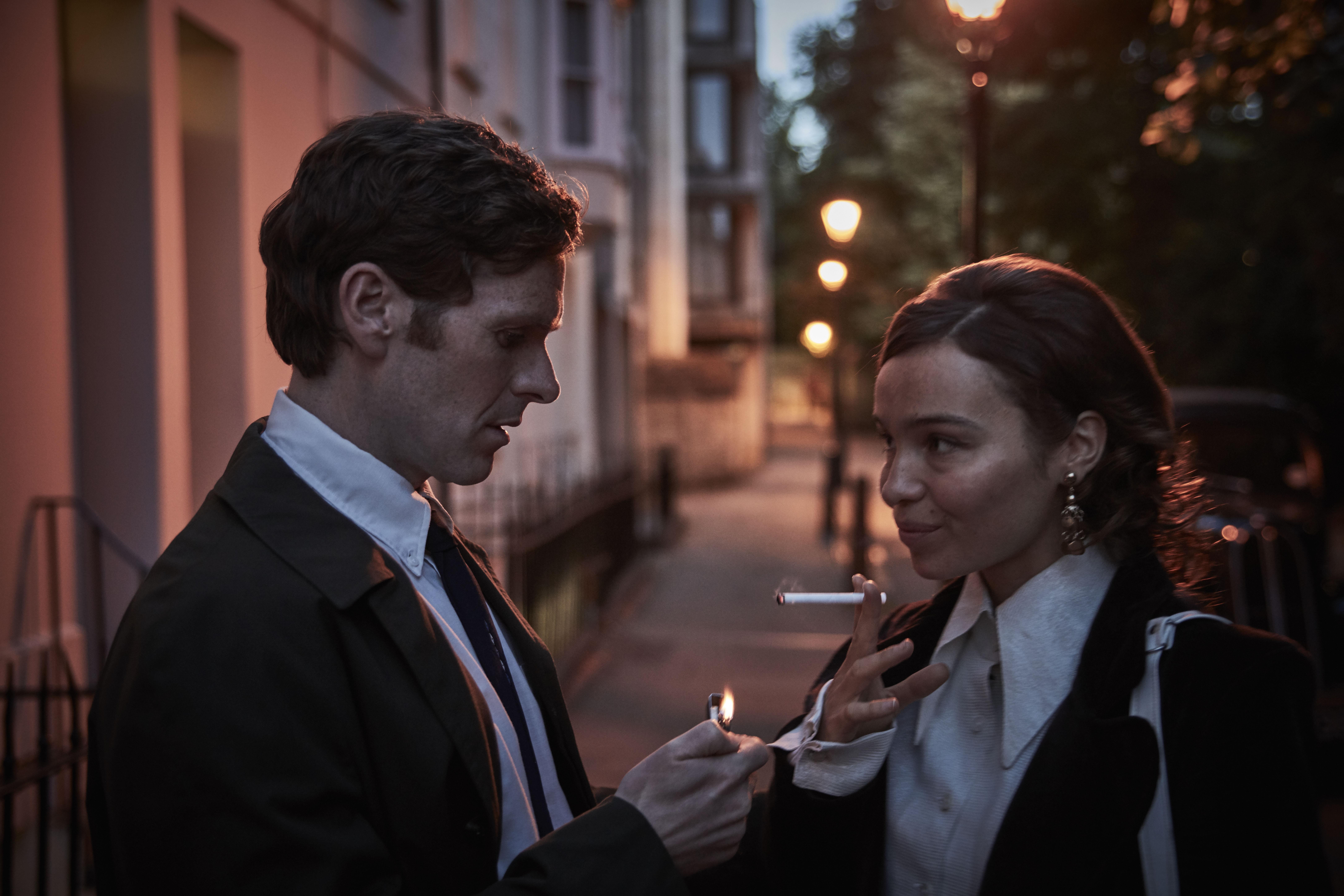 man helping smiling woman light cigarette standing on British street