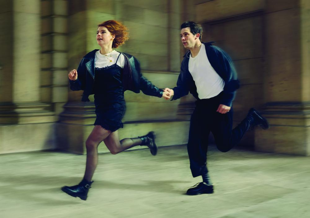 A man and woman running inside a hall