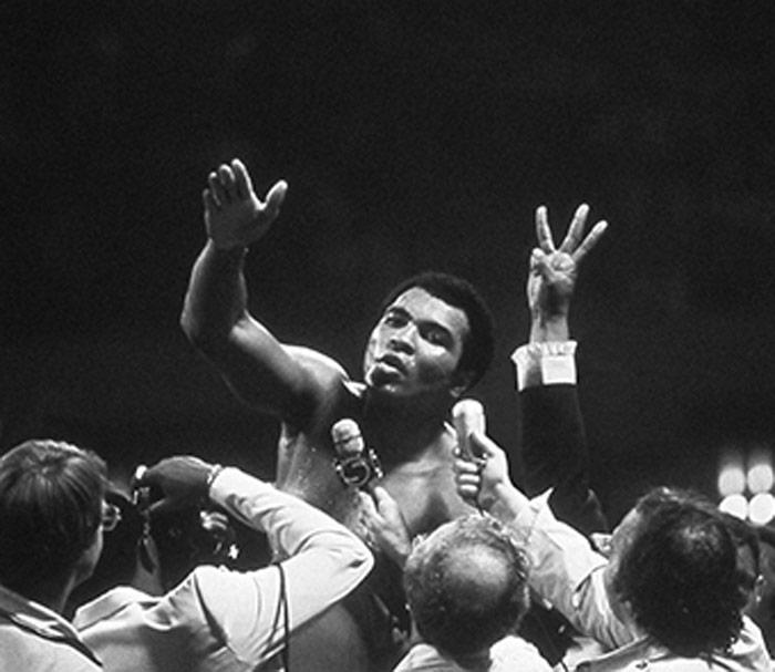 Ali speaking with excited group of reporters, black and white photo