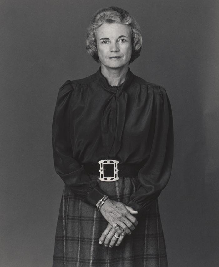 black and white photo of woman in smart skirt and long-sleeved shirt looking into camera