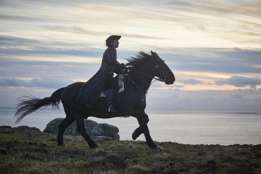 Poldark riding a horse next to a body of water