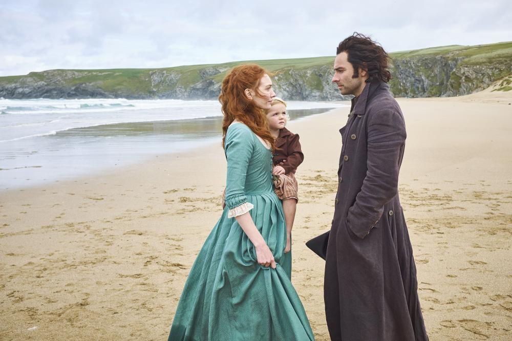 Man and woman on a beach dressed in fancy clothes