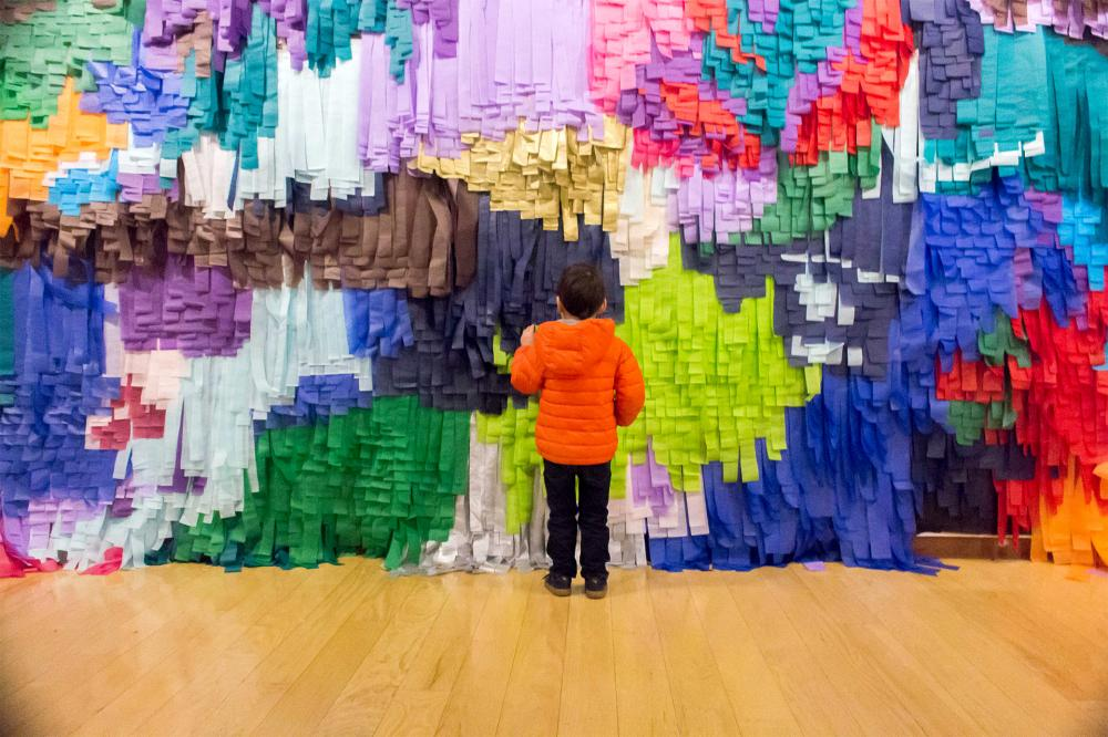 Child standing in front of a colored art wall.
