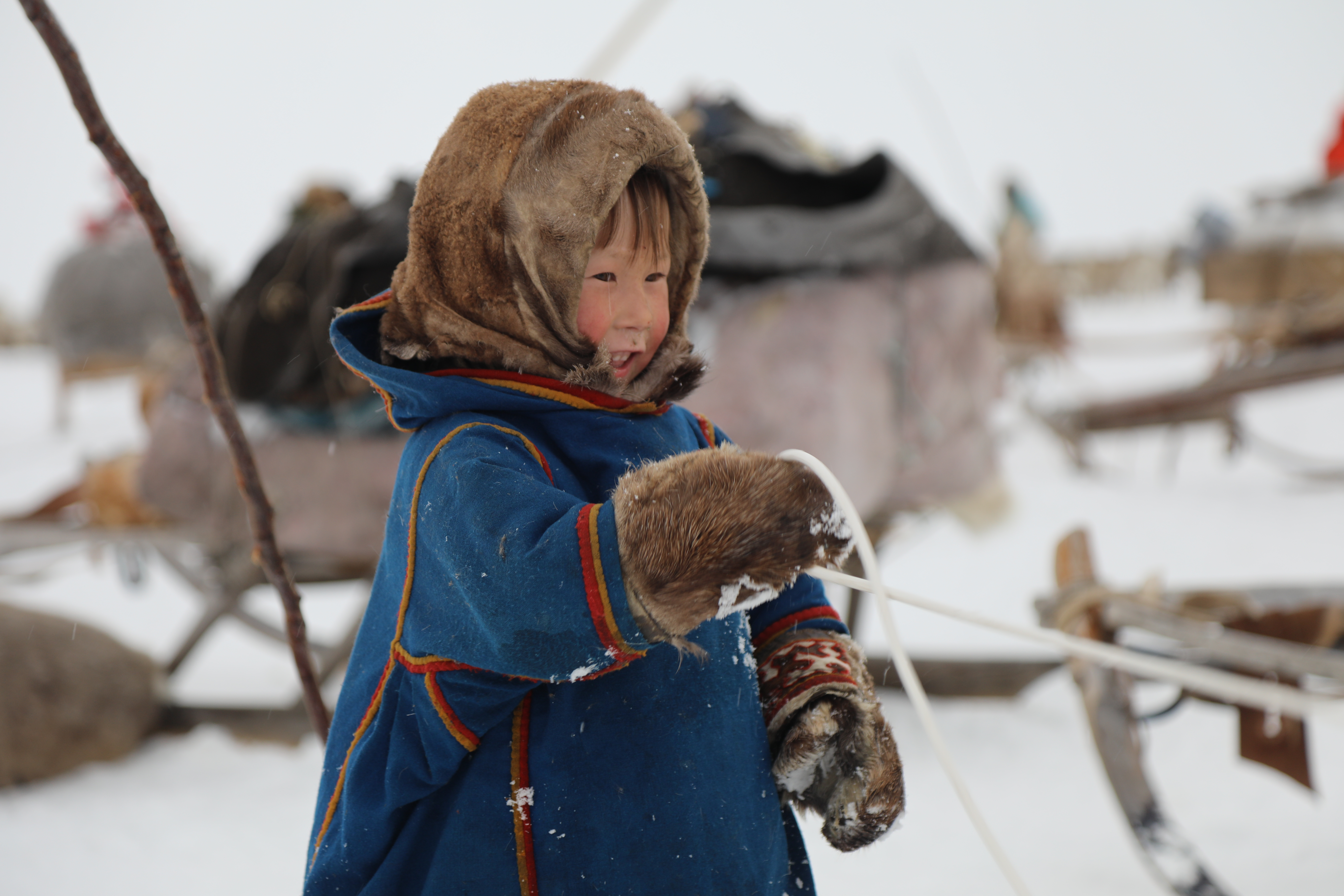 child wearing eskimo gear standing in the snow holding a rope