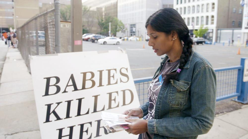 Women standing sadly in front of an anti-abortion sign.