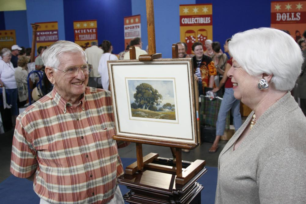 Two people by a painting at an auction
