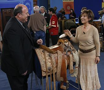 Two people looking at a saddle