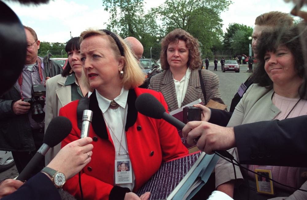 Distraught woman being uncomfortably surrounded by reporters with giant microphones