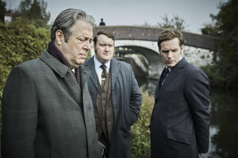 3 men in suits looking in disdain at the ground